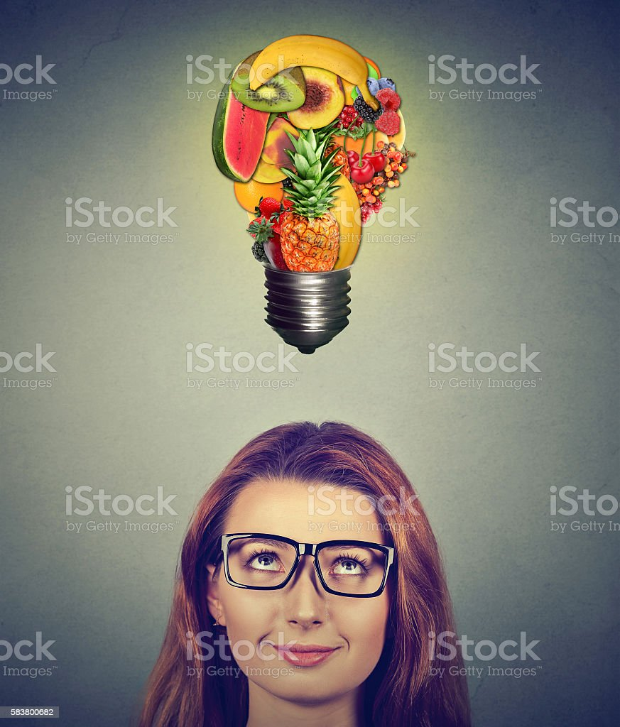 Woman looking up at fruits light bulb stock photo