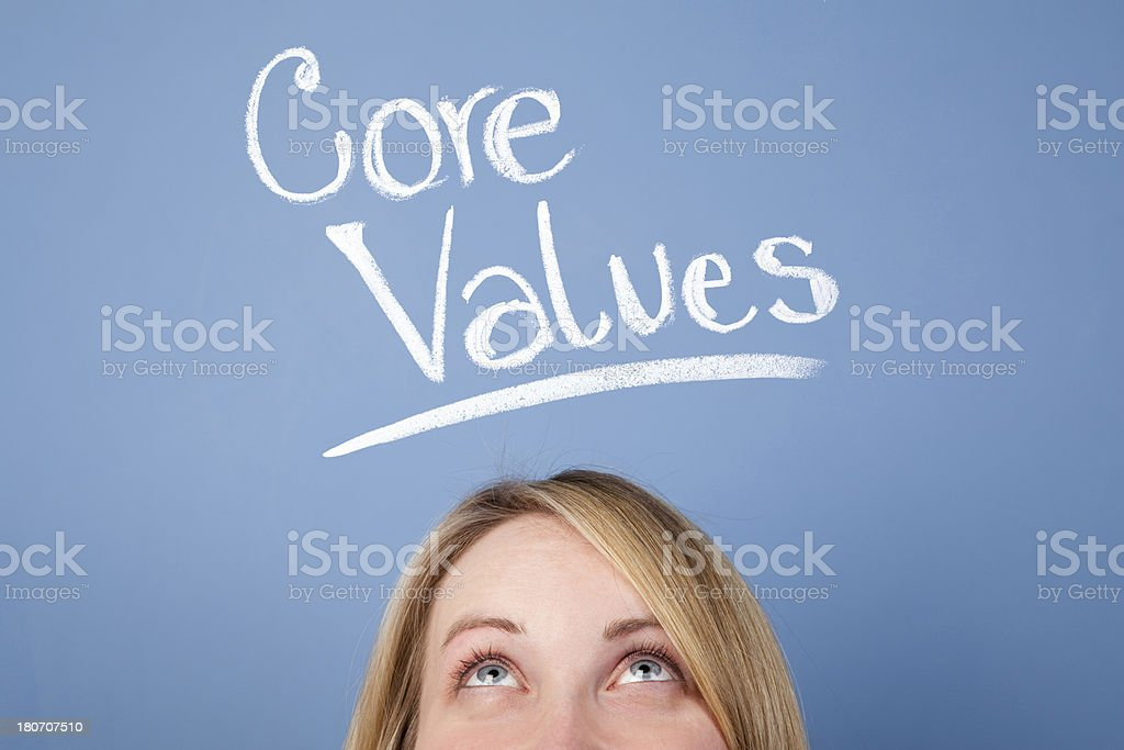 Woman looking up for the words of Core values on blackboard royalty-free stock photo