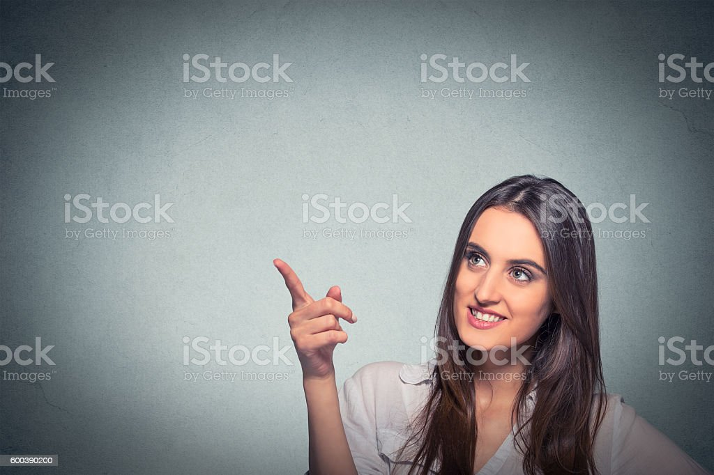 woman looking up pointing finger at blank copy space stock photo