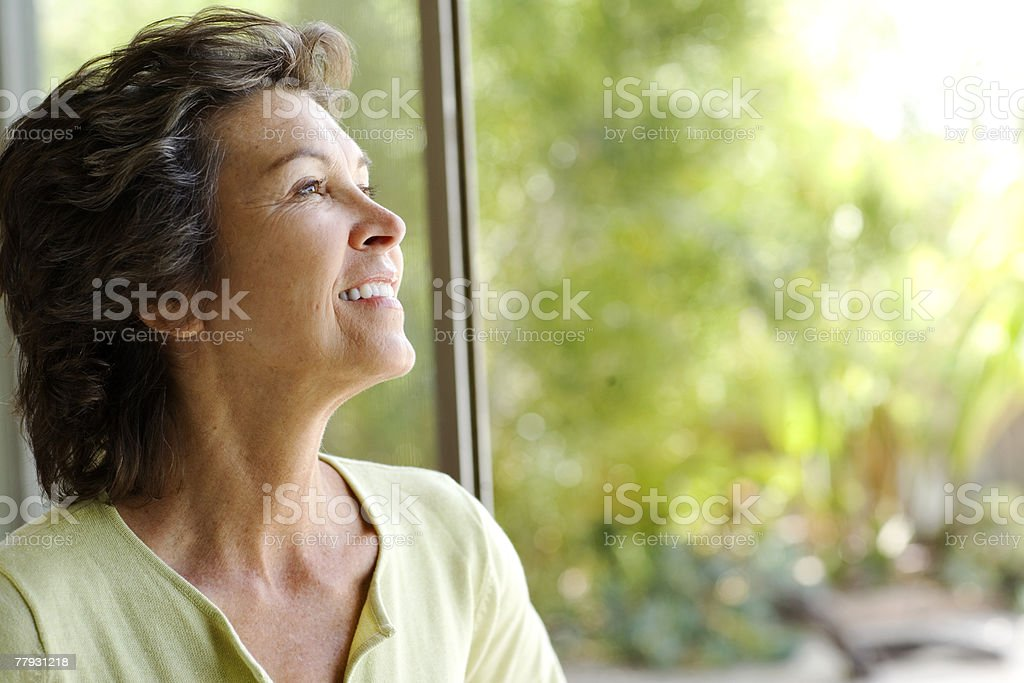 Woman looking up smiling in front of large windows stock photo