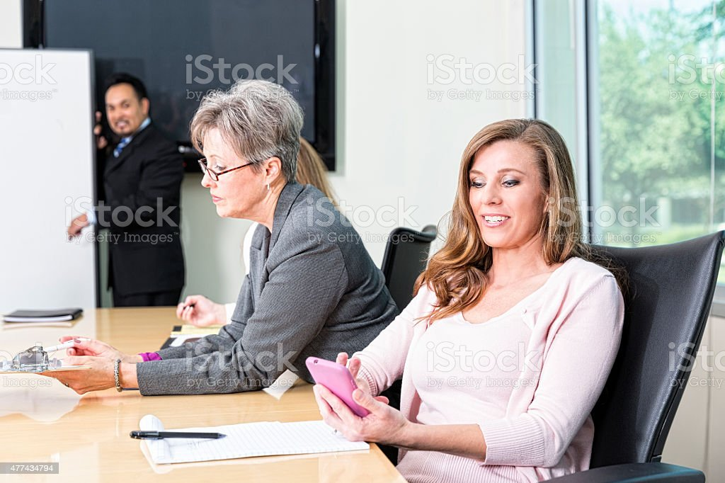 Woman Looks at Her Cell phone During Business Meeting stock photo