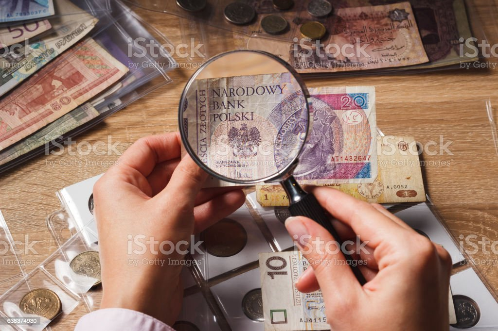 Woman looks at the Zloty through a magnifying glass stock photo