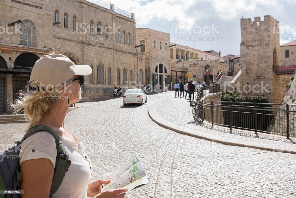 Woman looks at tourist map on city street stock photo