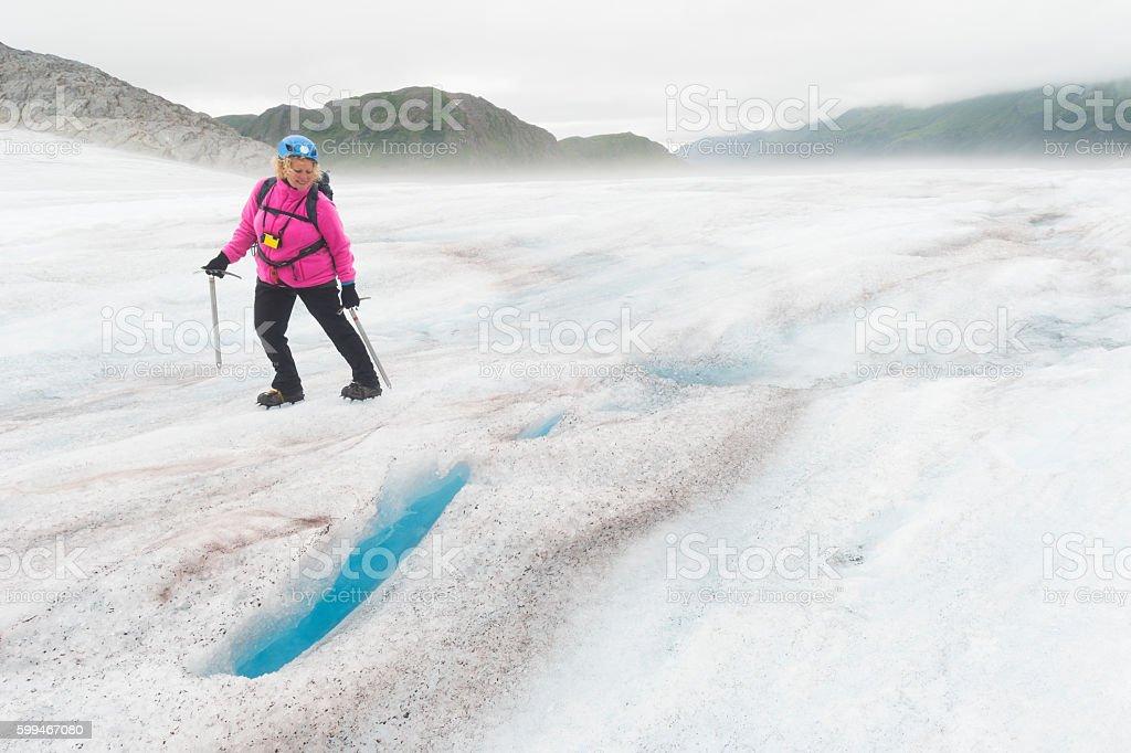 Woman looks into a crevasse stock photo