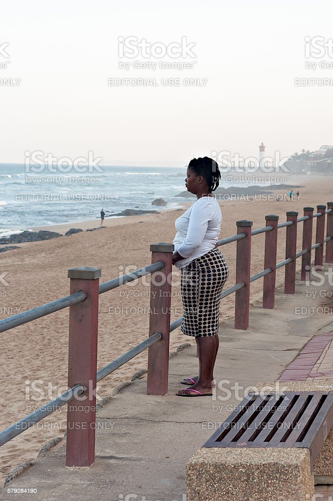 Woman looks out to sea stock photo