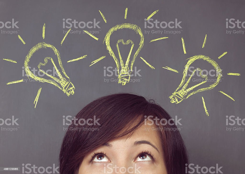 Woman looks up on light bulb stock photo