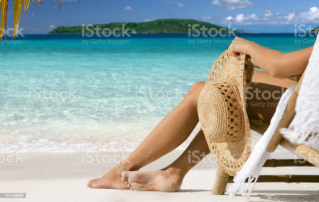 woman lounging at beach in paradise stock photo