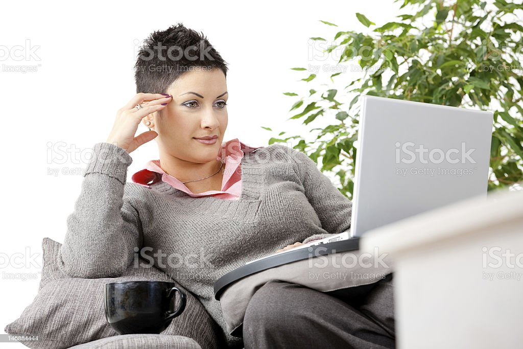 Woman lounging on the couch teleworking from home royalty-free stock photo
