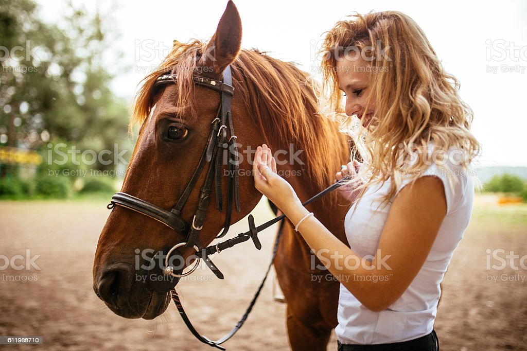 Beautiful girl with her horse in countryside on a nice summer day
