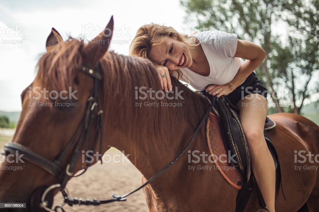 One woman, riding a brown horse, outdoors on a ranch.
