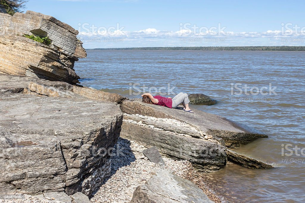 woman lying and relaxing on a boulder next to lake stock photo