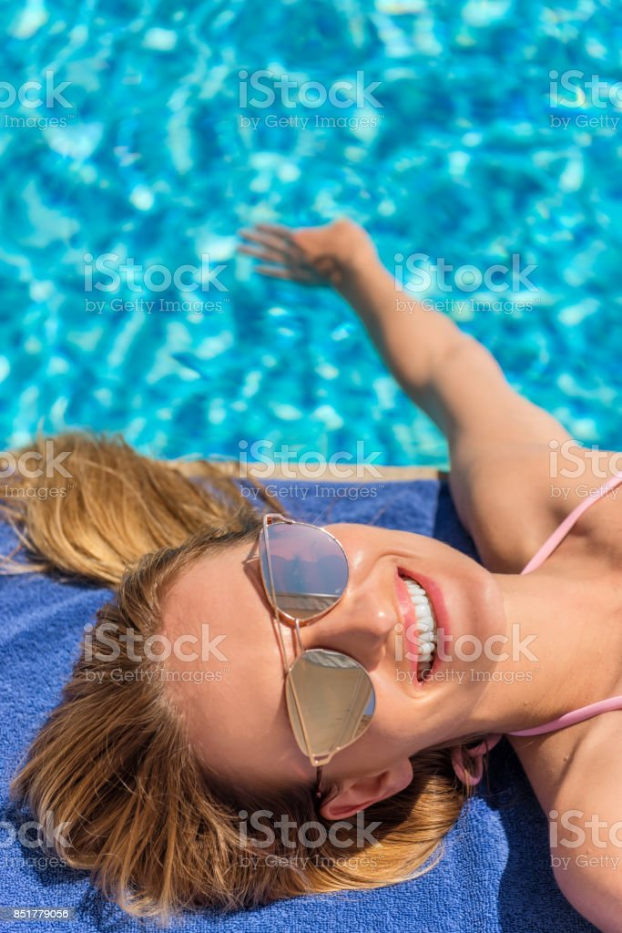 Vertical color portrait of pretty woman sunbathing at the edge of a...
