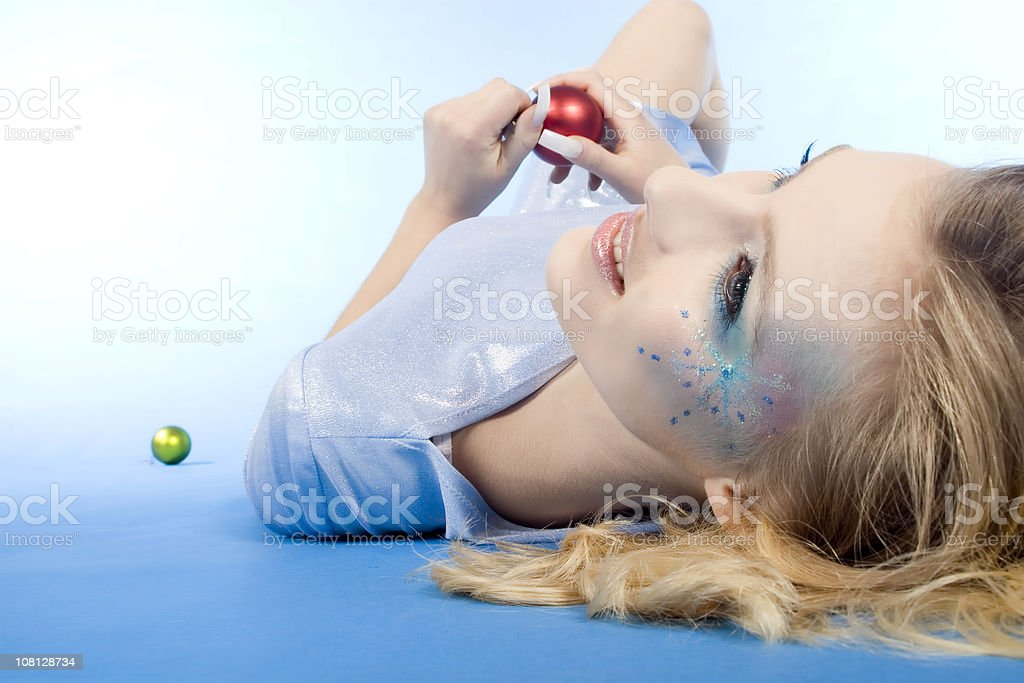 Woman Lying Down and Holding Christmas Decoration royalty-free stock photo