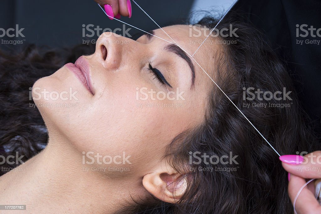 Woman lying down having her eyebrows threaded  stock photo