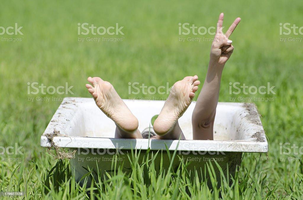 Woman lying down in a bathtub stock photo