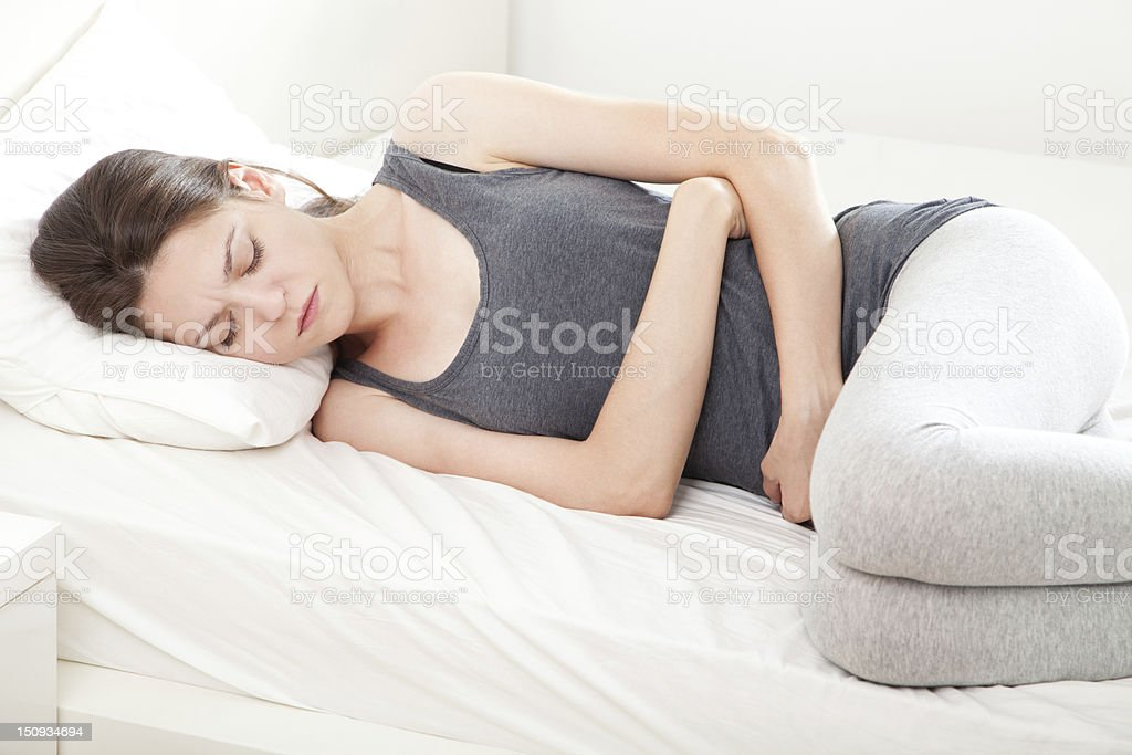 Woman lying down in bed clutching stomach with a grimace stock photo