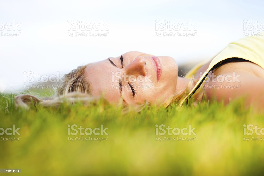Woman lying down in grass relaxing royalty-free stock photo