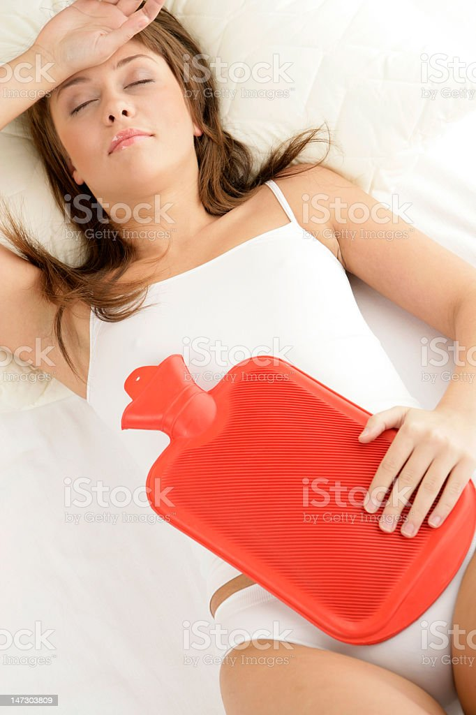 Woman lying down on bed with red hot water bottle on stomach royalty-free stock photo