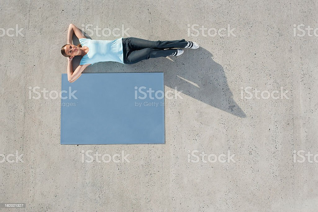 Woman lying down on ground with mirror and reflection stock photo