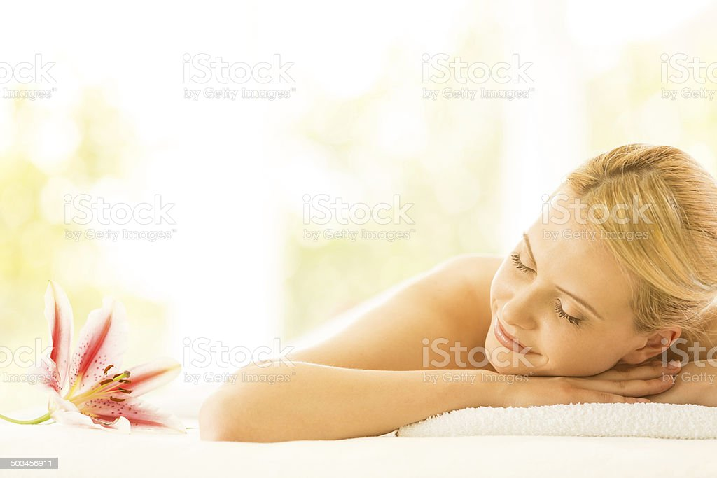 Woman lying down on massage table stock photo