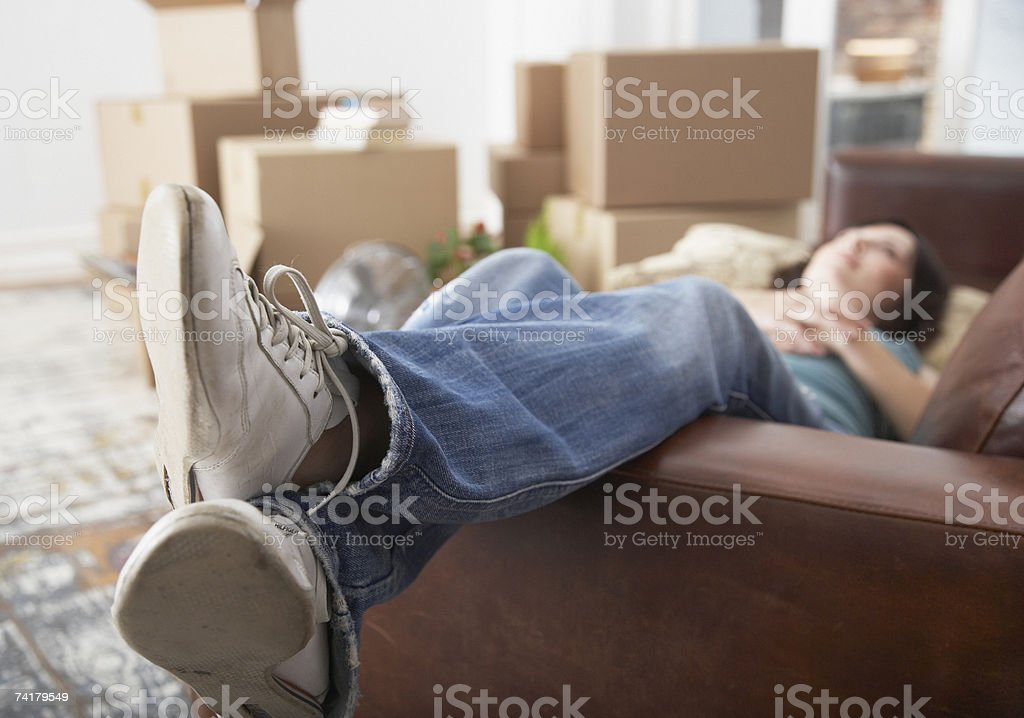 Woman lying down on sofa in home with cardboard boxes stock photo