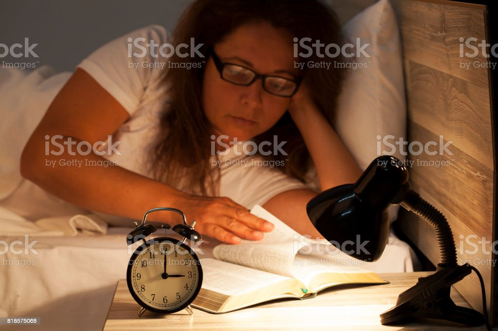 Woman lying in bed and reading  a book stock photo