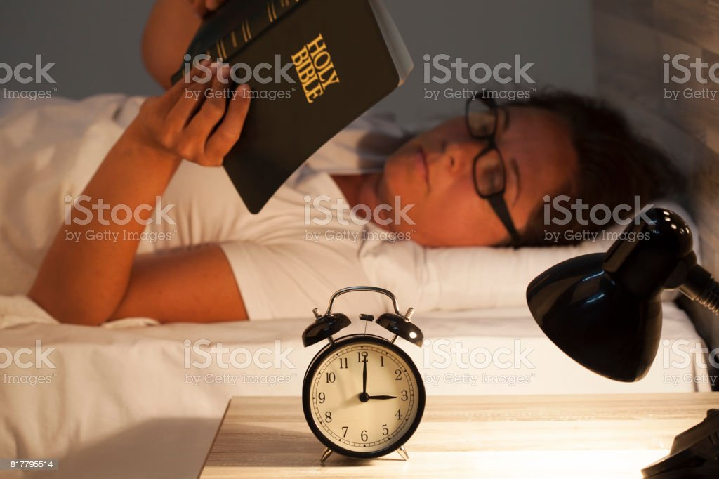 Woman lying in bed and reading  Bible stock photo