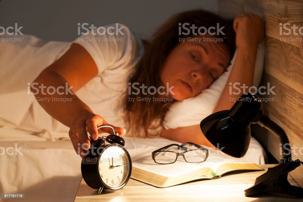Woman lying in bed suffering from insomnia stock photo