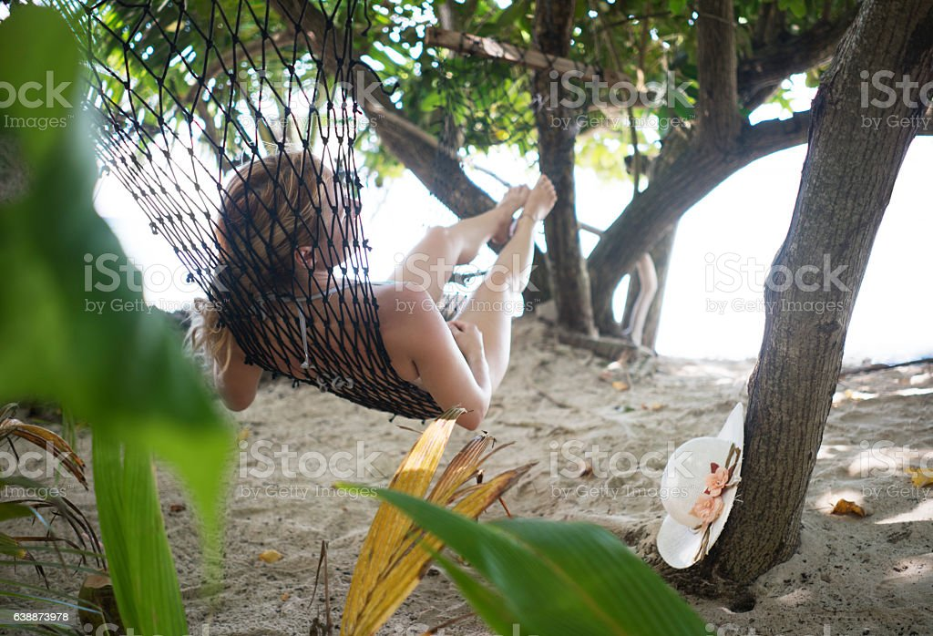 Woman lying in hammock during summer day at the beach. stock photo