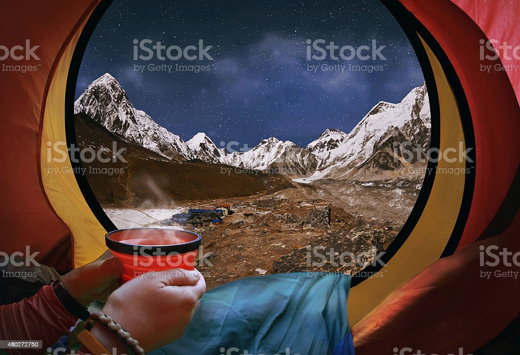 Woman lying in tent with coffee ,view of mountains stock photo