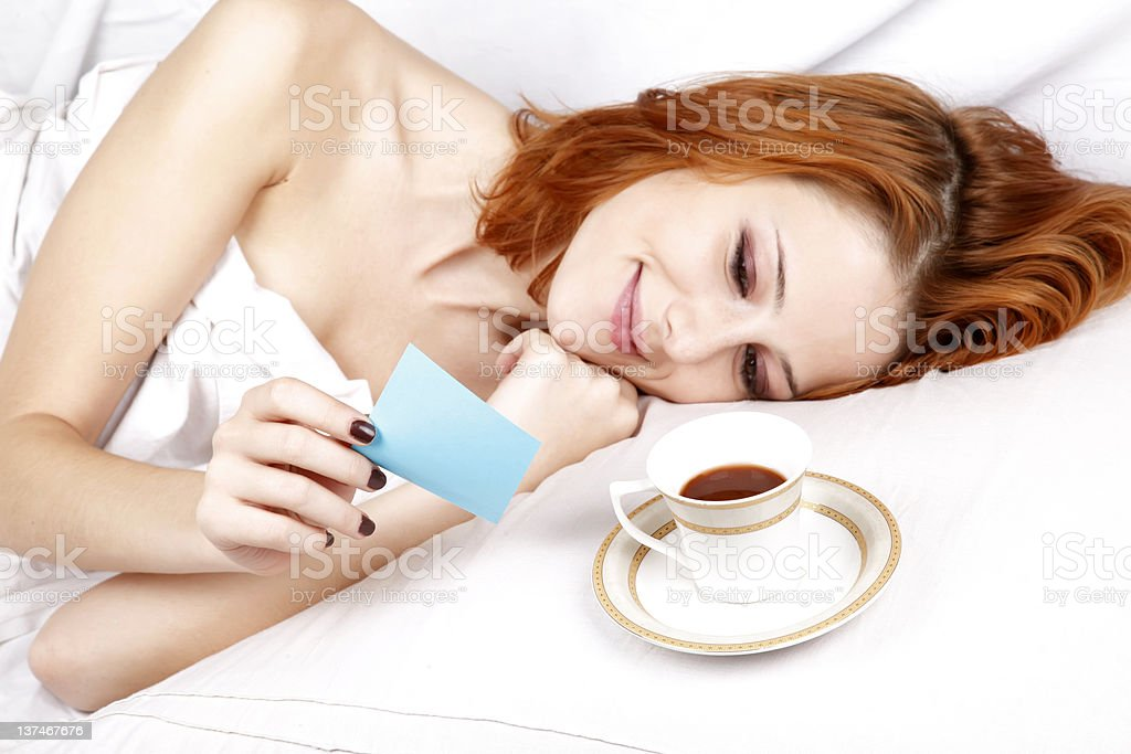 Woman lying in the bed near cup of coffee. royalty-free stock photo