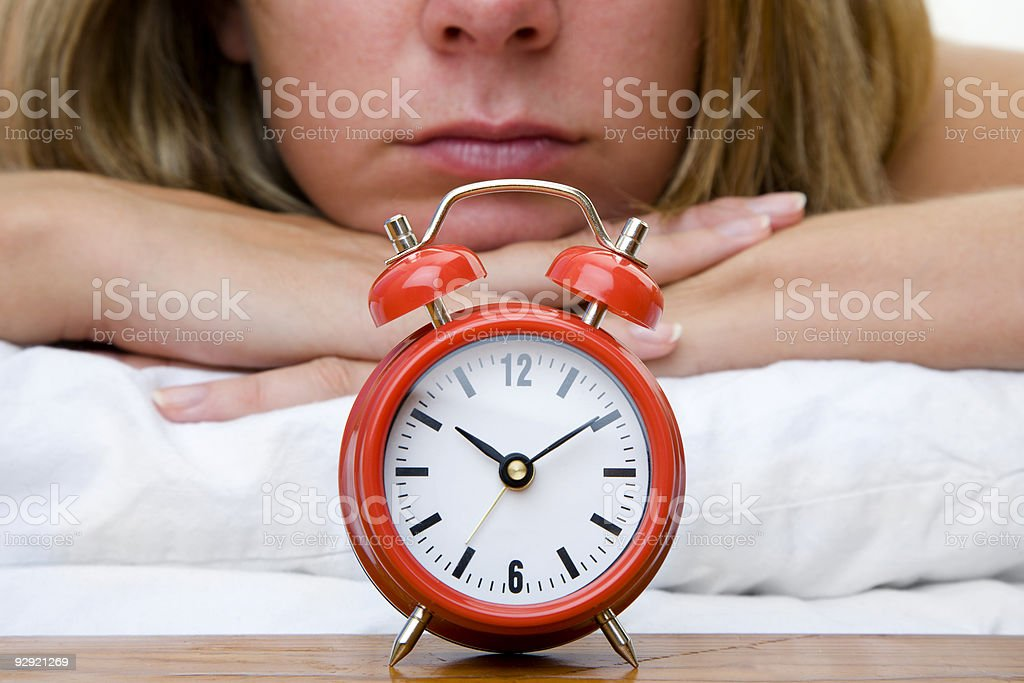 A woman lying on a comforter watching the back of a clock stock photo