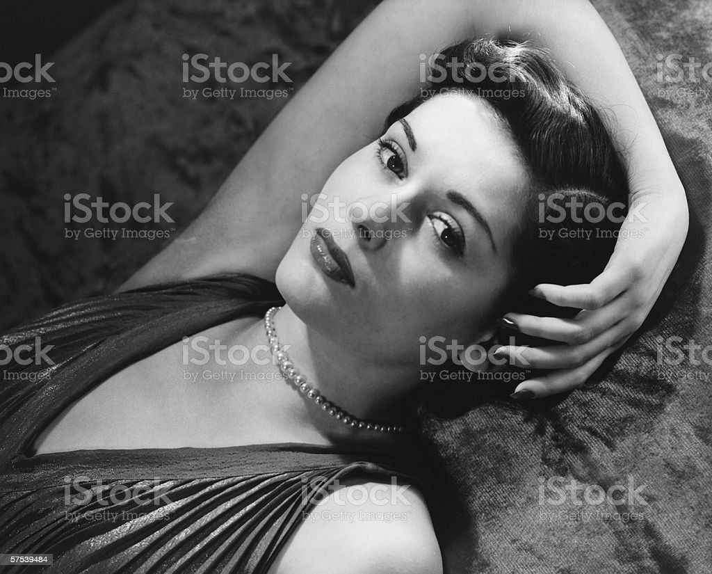 Woman lying on bed, (B&W), close-up, portrait stock photo