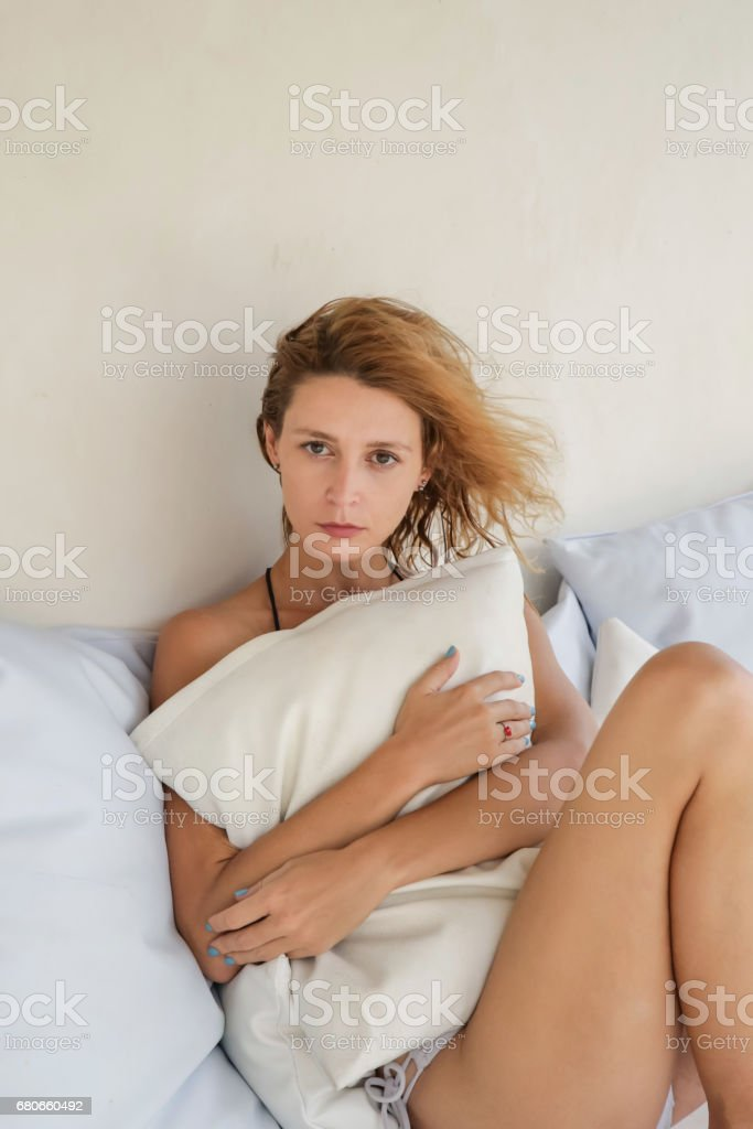 Woman Lying on Bed Hugging Pillow stock photo