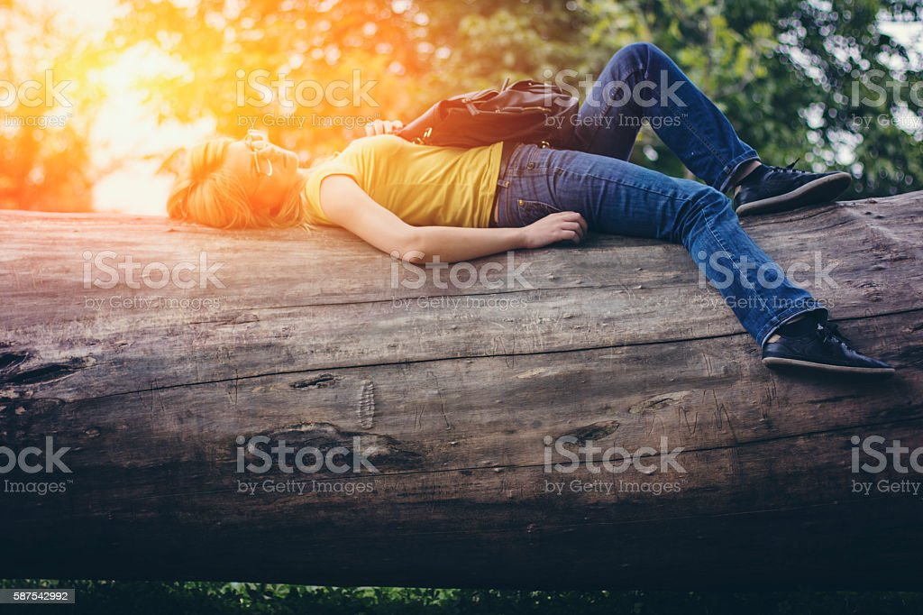 Woman lying on big cutted tree stock photo