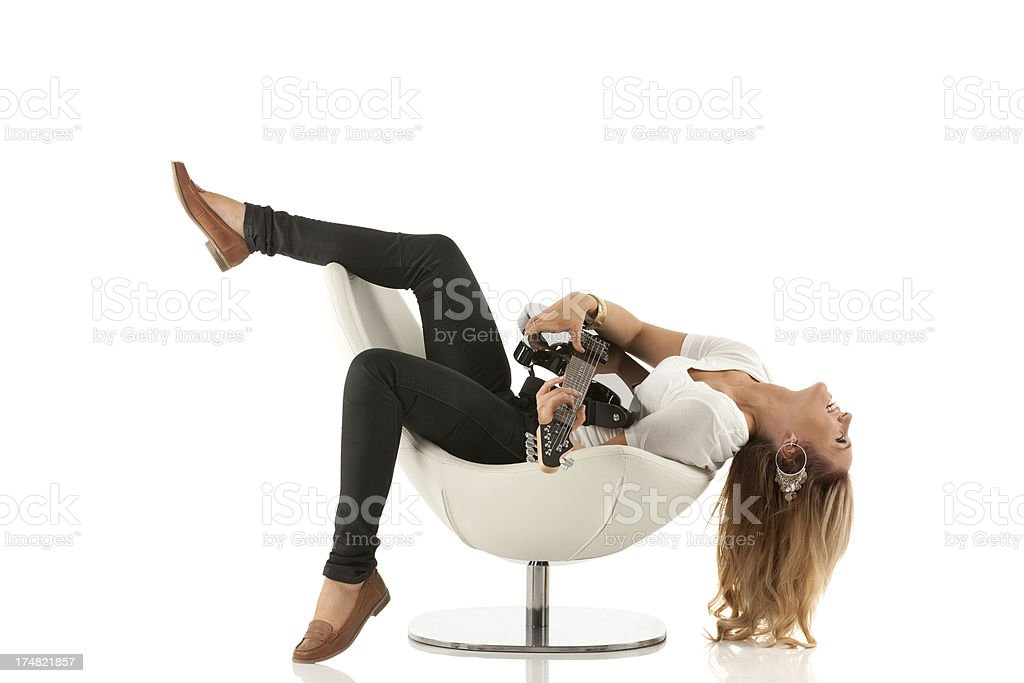 Woman lying on chair and playing a guitar royalty-free stock photo