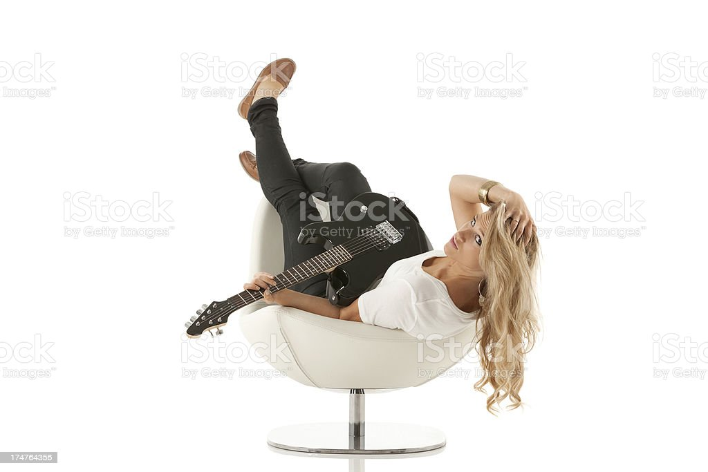 Woman lying on chair with a guitar royalty-free stock photo