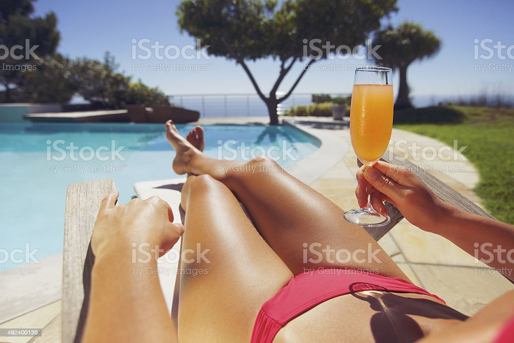Woman lying on deck chair with fruit juice stock photo