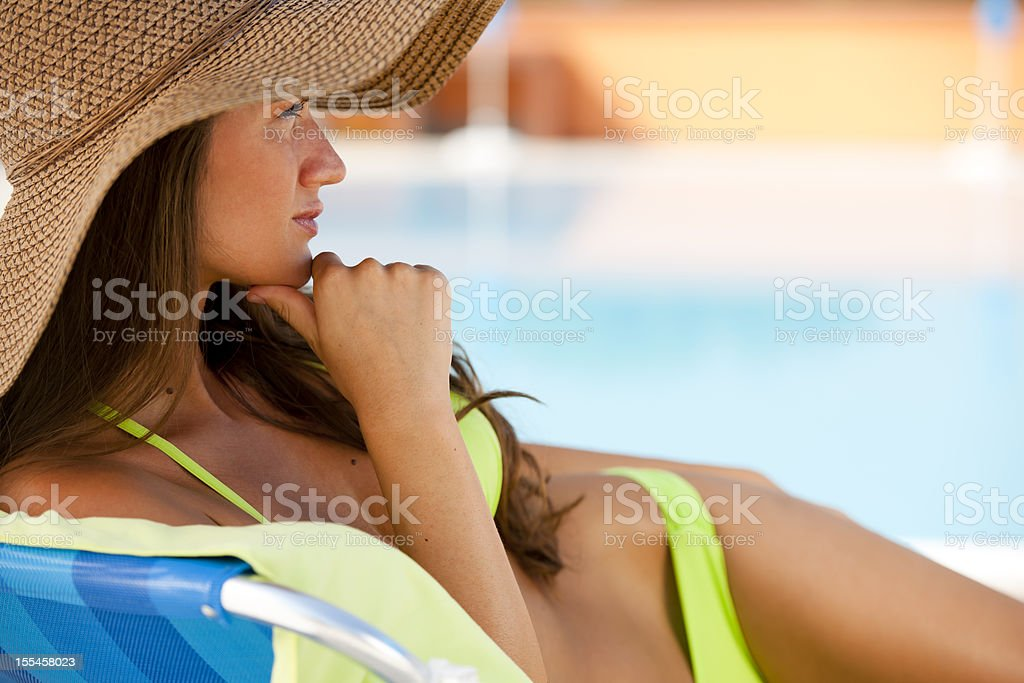Woman Lying On Deckchair By swimming-pool stock photo