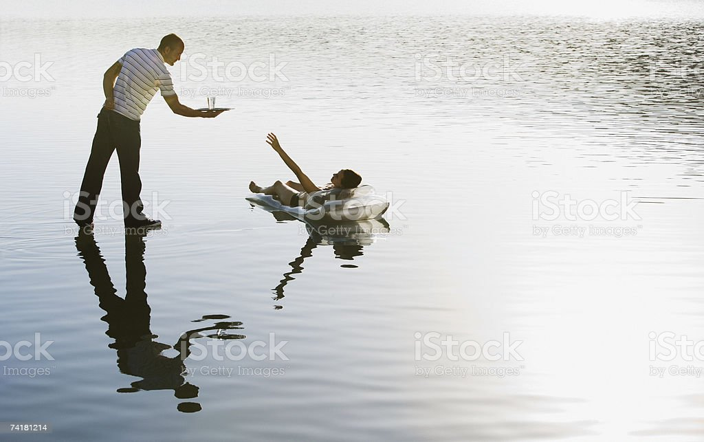 Woman lying on flotation device and man standing on water with beverage royalty-free stock photo