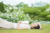 woman lying on grass field after she tired for reading