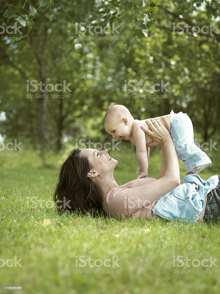 Woman lying on grass, holding baby boy royalty-free stock photo