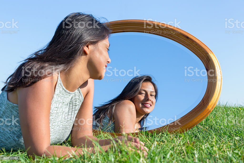 Woman lying on grass outside looking in mirror stock photo
