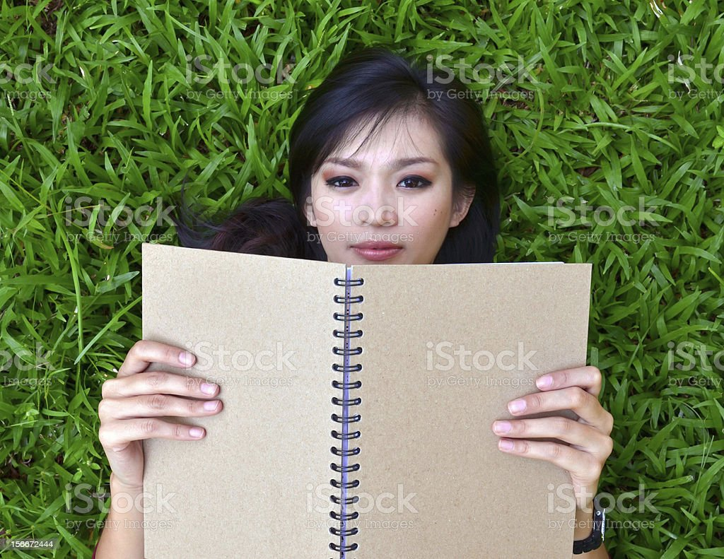 Woman lying on grass with a book stock photo