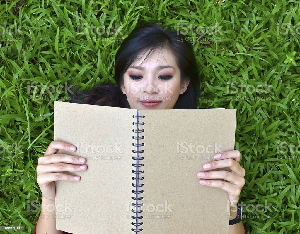 Woman lying on grass with  book stock photo
