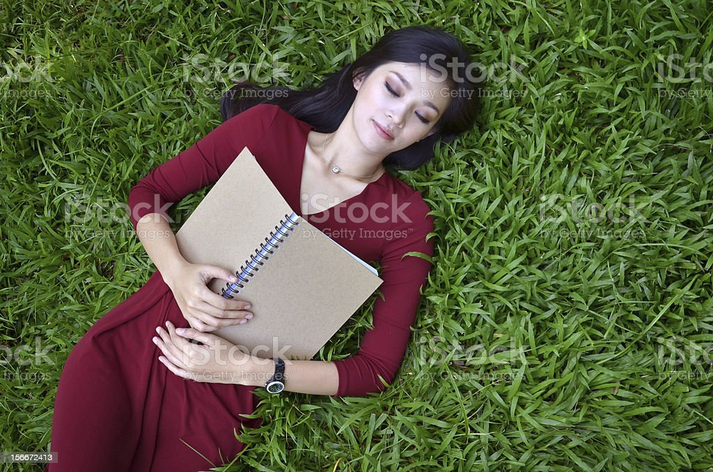 Woman lying on green grass with  book royalty-free stock photo