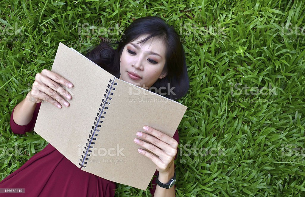 Woman lying on green grass with  book stock photo