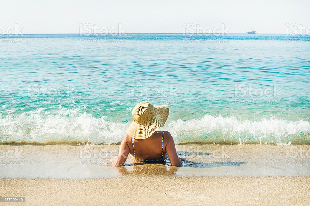 Woman lying on sand and enjoying clear blue sea waters stock photo