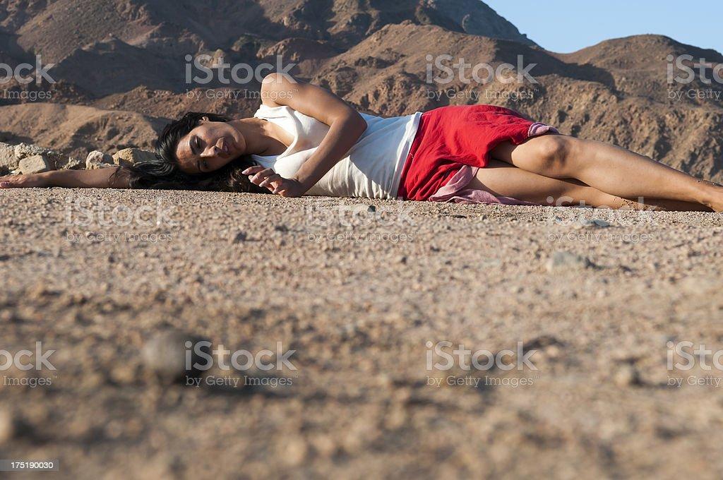 Woman lying on side in desert stock photo