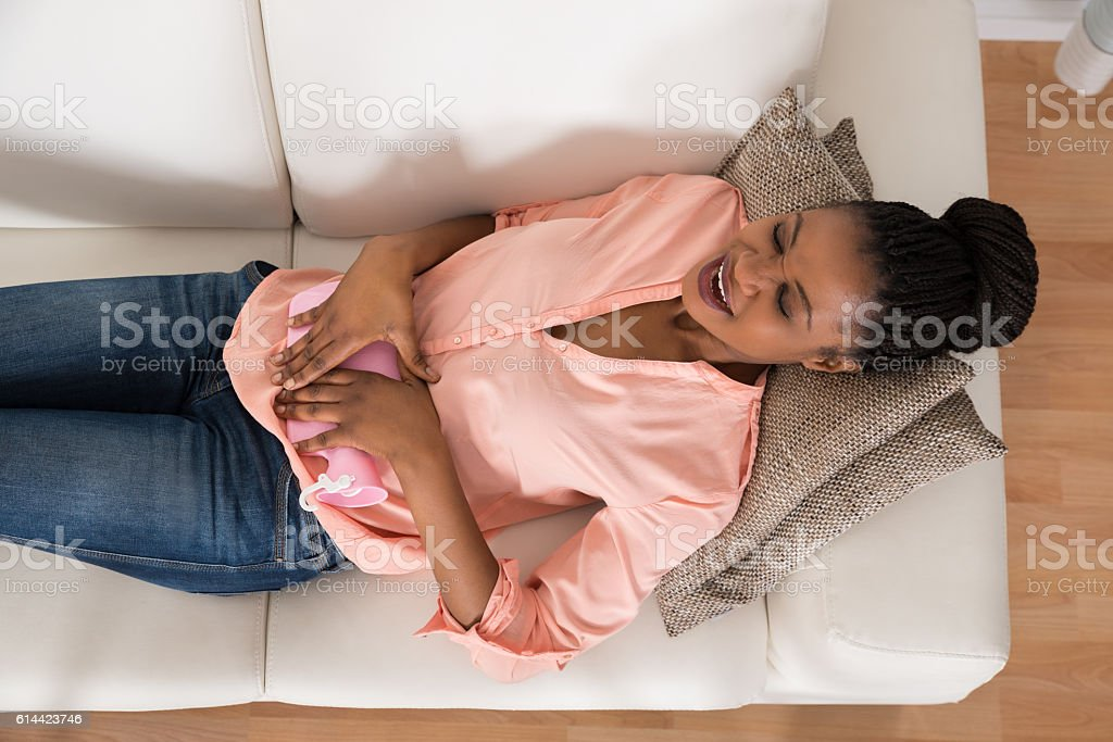 Woman Lying On Sofa With Hot Water Bag stock photo